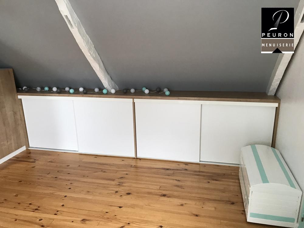 Fabrication et pose d'un agencement sous rampant de toiture. Les étagères et les portes coulissantes sont en partie basse. La penderie et les portes battantes sont en partie haute, y compris 1 miroir fixé sur une porte battante.